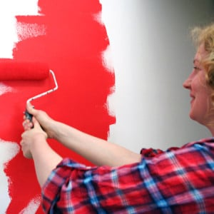 Rolling red paint on wall
